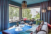 Extravagant living room in petrol blue with panoramic windows