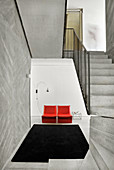 Red armchair, arc lamp and side table in foyer with concrete stairs in foreground