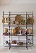 Metallregal mit Sammlung an Tonvasen, Basttellern und Büchern