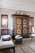 Antique painted cabinet flanked by two louvre windows