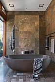 Freestanding bathtub in the bathroom with travertine tiles