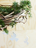 Hanging wreath of coniferous branches with homemade angel pendants