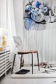 Stuhl vor der Wand mit einer Papierrolle mit aufgemaltem Bild