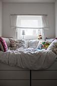Bett mit vielen Kissen auf zwei Kommoden unterm Fenster
