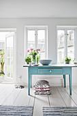 Alter blauer Tisch Sprossenfenstern und der Tür zum Garten