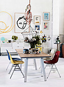Dining table with colorful chairs, pendant lamp with basket above, modern art on the wall