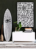 Paddle, surfboard and lowboard on wheels with modern art on top