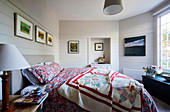 Patchwork bedspread on gray upholstered bed in bedroom with white wooden walls