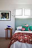 Bed with a high mint green headboard under a narrow, open louvre window