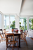 Dining table in a light-flooded beach house with floor-to-ceiling windows