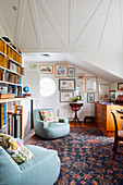 Two light blue armchairs next to bookcase in room under sloping ceilings