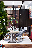Dining area with gray chairs in front of an antique, Moroccan door as a room divider, decorated Christmas tree in the foreground