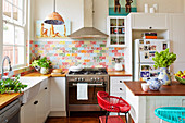 White fitted kitchen with wood worktop wood and colorful wall tiles