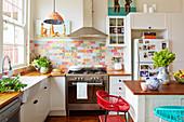 weiße Einbauküche mit Holz-Arbeitsplatte Holz und bunten Wandfliesen