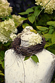 Wreath of wicker and hydrangea around neck of tailors' dummy