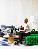 Blond woman sitting on green ottoman, gold-colored coffee table and gray sofa in living room