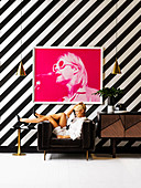 Photography in pink on a black and white striped wall, blonde woman in a brown armchair