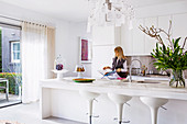 White fitted kitchen with island and bar stools, woman in the background