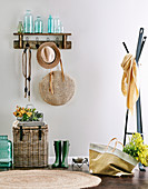 Wall coat rack with bottle collection, hat and handbag, including wicker chest and rubber boots, next to it a coat rack