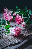 Rosa Rosen auf rustikalem Holztisch