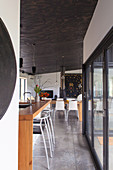 Barhocker an Frühstückstheke aus Holz vor Terrassentüren