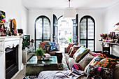 Sofa mit bunten Kisssen und Couchtisch vor Kamin, im Hintergrund geöffnete Rundbogentür