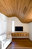 Undulating, wood-clad ceiling in living room
