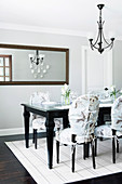 Elegant dining area: dark table, chairs with covers and wall mirror