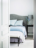 Glance into the bedroom on a double bed with a gray headboard and a clothes bench