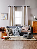 Gray upholstered sofa with blankets and pillows in front of the window, seat cushion and chair as storage furniture on carpet