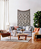 Gray upholstered sofa with pillows, coffee table, armchair and chair as storage furniture