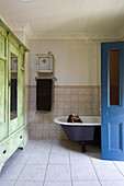 Green wardrobe in bathroom and open blue bathroom door