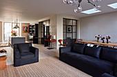 Dark upholstered furniture in open-plan interior