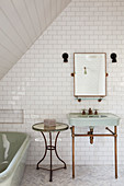 Vintage-style washstand, side table and bathtub in tiled bathroom
