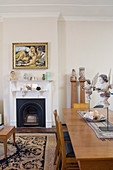 Cherubs on dining table, artworks and fireplace in open-plan interior