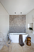 Free-standing bathtub and classic chair in narrow bathroom