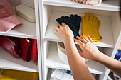 Women's accessories on open shelves in dressing room; hand picking up gloves