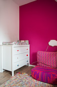 Changing mat on white chest of drawers and beanbag in room with hot-pink wall