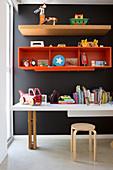Regale und Schreibtisch an schwarzer Wand im Kinderzimmer