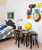 Kinderbilder und Trophäen über dem Tisch mit Stühlen im Kinderzimmer