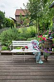 Cherries, cushions and crocheted blanket on white bench on terrace