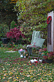 Chair with cushions and blankets, hydrangea, silver teapot and tray in autumnal garden