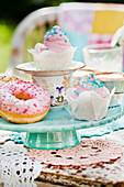 Pastries with colourful decorations on cake stand made from stacked crockery