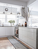 Open kitchen with white glossy fronts and wooden floor