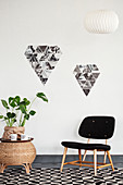 Chair, houseplant on side table and arrangement of black-and-white photos on wall