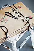 Vintage drawing folder labelled 'Herbarium' on stool