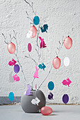 Vase of branches decorated with paper cut-outs and Easter eggs