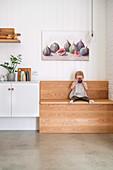 Kleines Mädchen sitzt trinkend auf einer Holzbank in der Küche