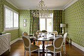 Dining room in shades of green with graphic pattern on wallpaper