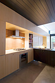 Modern fitted kitchen in pale wood with dark wooden ceiling